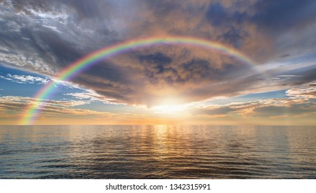 Storm on the sea with amazing rainbow at sunset