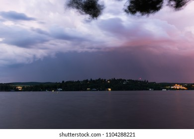 "Storm over Brno city in hot summer evening. Long time exposure with blurred water and leaves. Photo taken from dam called ""Prygl"" near Brno city during blue hour. Moravia, Czech republic, Europe."