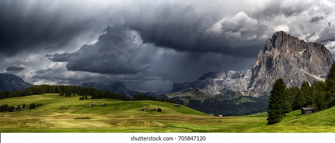 storm over the mountains Dolomiti in the summer season with green meadow illuminated of the Sun