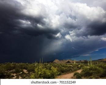 Storm passing over desert landscape.