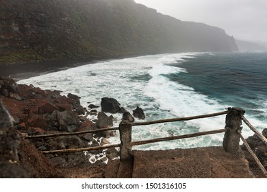 Storm and rain with tall waves hitting the beach at Playa de Nogales beach in La Palma, Spain.