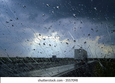 Storm seen through the windshield, with big rain drops