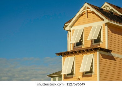 Storm shutters shade windows on a beach house on a sunny day in the Outer Banks of North Carolina, USA, for themes of hurricanes, weather, preparedness
