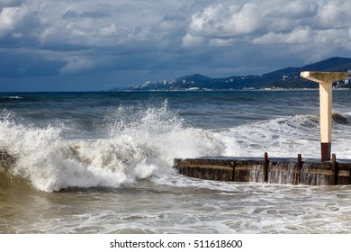 Storm in sunny weather, against a background of mountains and the resort of Sochi. Waves lapping on the beach.