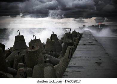 Storm surf breaking on breakwater.