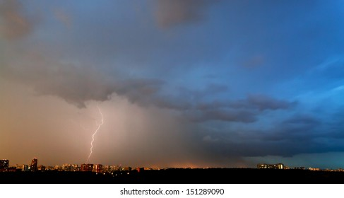 storm and thunderbolt over city in summer evening