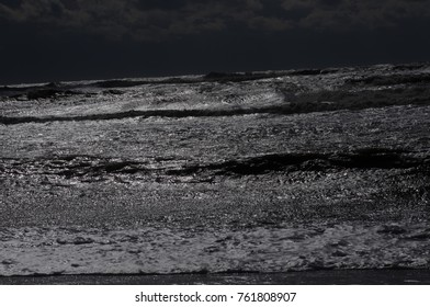 Storm wave rolls ashore at night in the moonlight