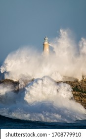 Storm waves breaking against the island of the Mouro lighthouse.