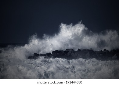 Storm waves over a pier in the north of Portugal. Black and white toned blue.