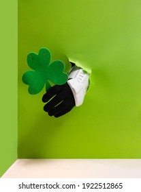 Stormtrooper hand is holding green clover from a bright green wall background.