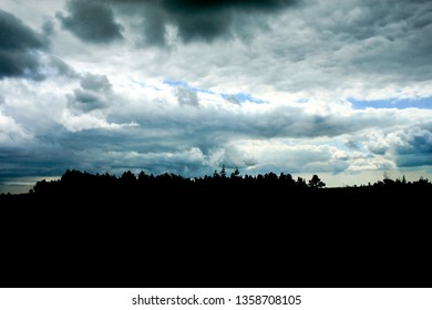 Stormy clouds and a forest in silhouette