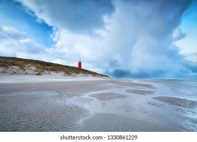 stormy clouds over red lighthouse on North sea coast, Holland