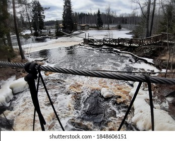 stormy and formidable with red water and white foam Akhvenoski waterfalls among the trees in Ruskealla. Karelia. Russia.