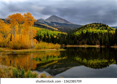 Stormy mountain scene over Wilson Peak near Telluride Colorado on fall afternoon with yellow aspen trees lining shore and reflecting in water