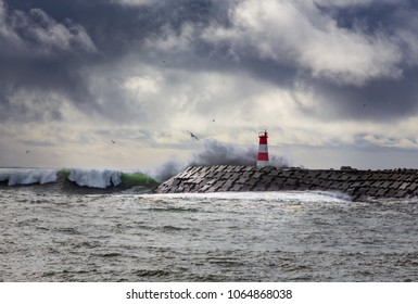 Stormy ocean with big waves crashing into a lighthouse in Portugal