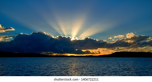 A stormy radiating crepuscular rays blue, grey and white coloured cumulonimbus cloudy sunrise seascape over sea water with water reflections and ocean sunbeams. Gosford, New South Wales, Australia.