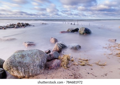 stormy sea with colorful stones on the beach. The boat's bridge is almost buried under water. long exposure shot.
