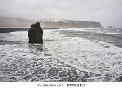 Stormy sea on the background of the faded cliffs and the cloudy sky in Iceland. There is a lonely rock on the beach. Horizontal.