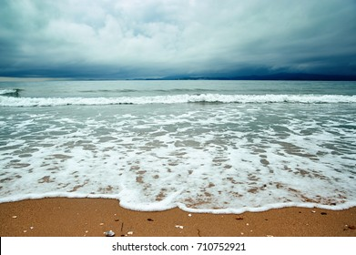 a stormy sea, storm clouds, empty beach on a summer day