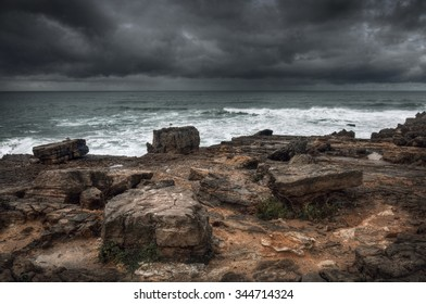 Stormy seascape with rocks in the foreground and dramatic cloudy sky