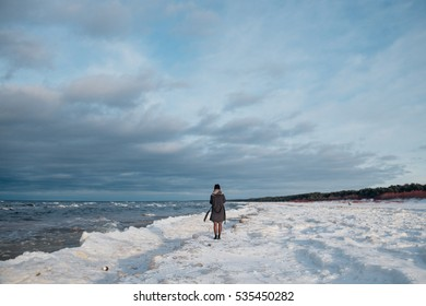 Stormy seaside in winter time. Girl standing backwards and watching sea. Woman waching sea