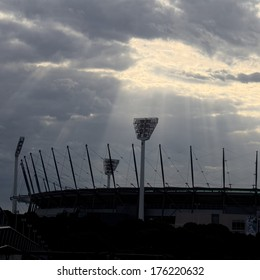 stormy skies looming over a cricket ground with sun rays