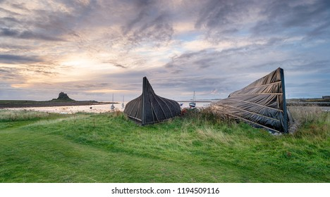 Stormy skies over upturned old boats used as boathouses on Lindisfarne on the Northumberland coast