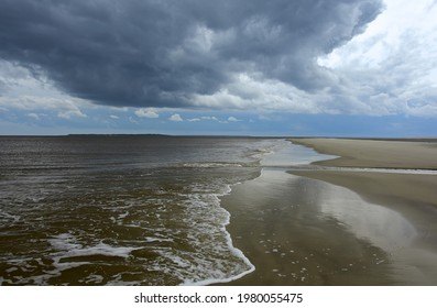 stormy skies, waves and  tidal flats at low tide on south end beach  on jekyll island, georgia