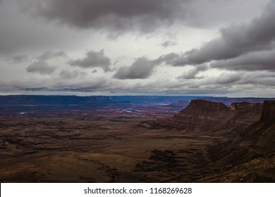 The stormy sky is attempting to obscure the cliff below and to the right, at the Needles Overlook near Monticello, Utah.