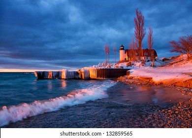 A stormy sky creates a dramatic scene at Point Betsie Lighthouse along the Lake Michigan shoreline. A setting sun scatters evening light on the waters surface, lighthouse and waves.