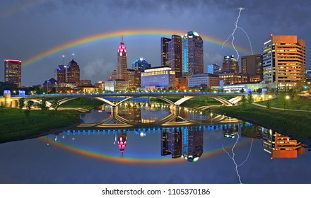 A stormy sky over the Columbus Ohio skyline with a rainbow, lightning bolt, and city lights reflecting onto the Scioto River, with the Rich Street bridge in the foreground.