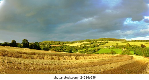 Stormy sky over a field of harvested corn, looking towards Painswick Beacon, The Cotswolds, Gloucestershire, United Kingdom