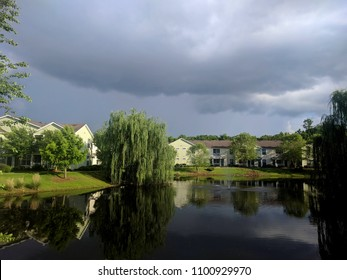Stormy Sky over Pond - Photograph of a stormy summer sky over some buildings and a pond with Weeping Willow trees at the edge of the pond.