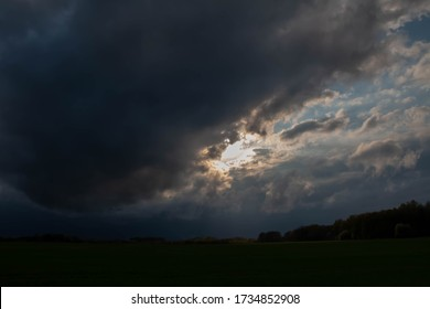 Stormy sky with rain clouds or smoke from a fire black looming clouds of smoke with red reflections and bright white gaps
