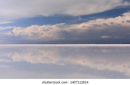 Stormy sky and reflections of clouds in shallow water. Main focus on clouds.   Salar de Uyuni - Altiplano, Bolivia, South America. Photo does not noise or lens dust. It is pieces of salt foreground.