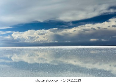 Stormy sky and reflections of clouds in shallow water of Salar de Uyuni. Main focus on clouds.  Altiplano, Bolivia, South America. Photo does not noise or lens dust. It is pieces of salt foreground