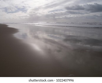 Stormy sky, at sunset, reflected on the surface of the water tide on a sandy Atlantic beach with the sun illuminating white waves, in winter in South West France, near Cousseau