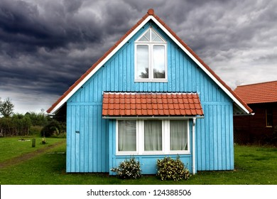 A stormy sky surrounds a small and peaceful blue wooden house