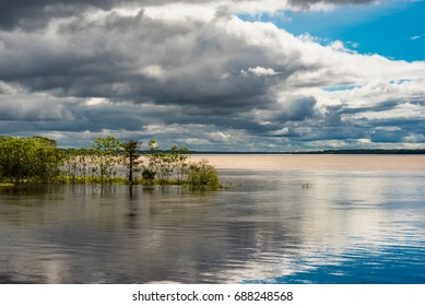 Stormy skys and mixed sunshine at the confluence of the Amazon river and the Rio Maranon and Rio Ucayali