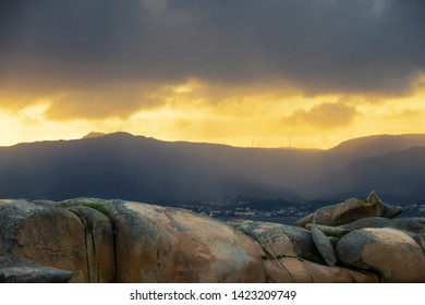 Stormy sunset over Curota mount on Barbanza range from the coastal rocks of Punta Cabalo Cape in Arousa Island