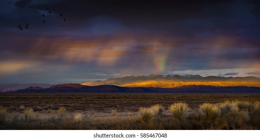 Stormy Sunset with rain and rainbow in the desert with light on mountain range.  Fallon, NV