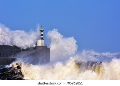 Stormy wave over lighthouse and pier of San Esteban de Pravia in Asturias, Spain.