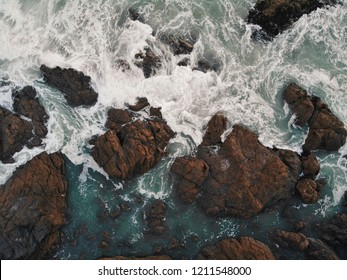 Stormy waves crashing into rocks on the rugged coastline in Cornwall