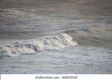 stormy waves runing towards a beach lit by a low sun.