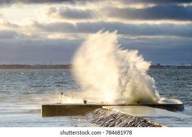stormy weather at Baltic sea coats. Wave splash at the pier on a stormy day. Tallinn skyline on the background.