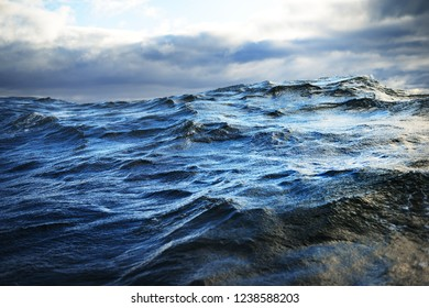 Stormy weather on the Baltic sea at sunset. Dark blue sky with lots of clouds. Waves and splashes. Latvia