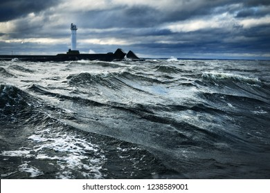 Stormy weather on the Baltic sea at sunset. Dark blue sky with lots of clouds. Waves and  splashes. Lighthouse in the background. Latvia