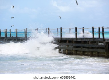 Stormy weather on the shores of the Caribbean sea. Big wave hitting the wooden bridge. Strong wind, dramatic sky. Water splashing on the pier.