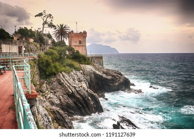 Stormy weather on the Tigullio gulf, view from the sea promenade  on the rocky coast of Genoa Nervi with the medieval Gropallo tower  built in the 16th-century as a watchtower for pirates.