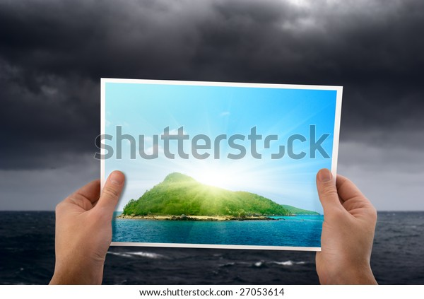 stormy weather and photo of tropical island in hands